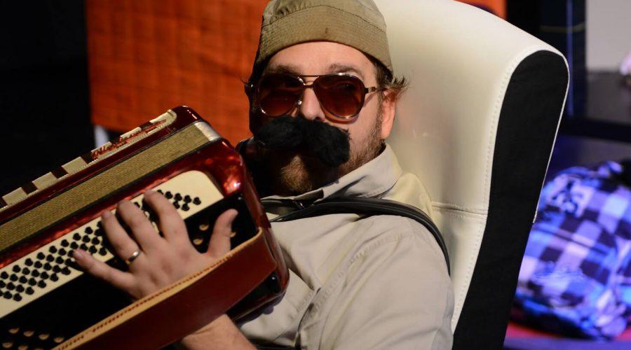 גבר עם כובע צמר ושפם מנגן באקורדיון