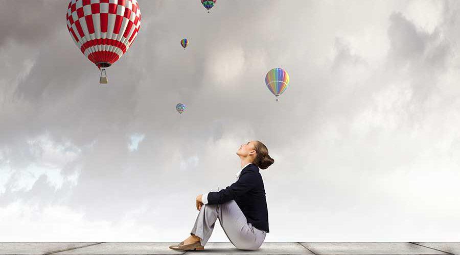 אישה יושבת על חומה ומתבוננת בכדורים פורחים בשמיים