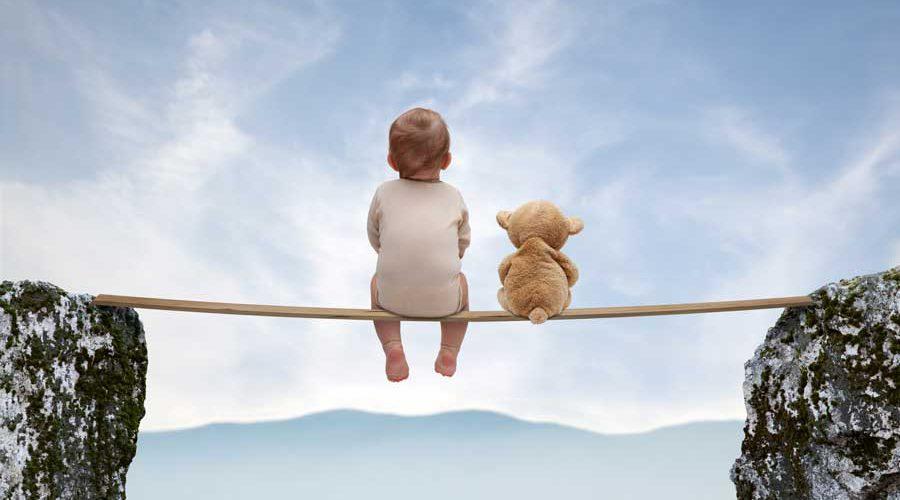 תינוק ודובי ישובים על קרש בין שני סלעים