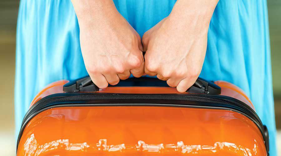 ידי אישה מחזיקות מזוודה
