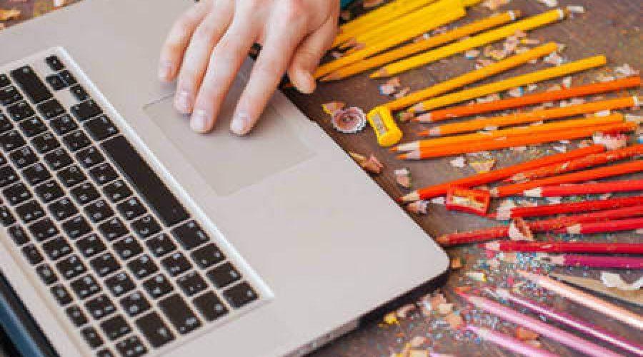 לפטופ ועפרונות צבעוניים סביבו