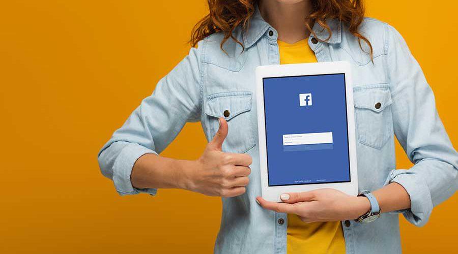 אישה מחזיקה טאבלט ומסמנת לייק - פייסבוק