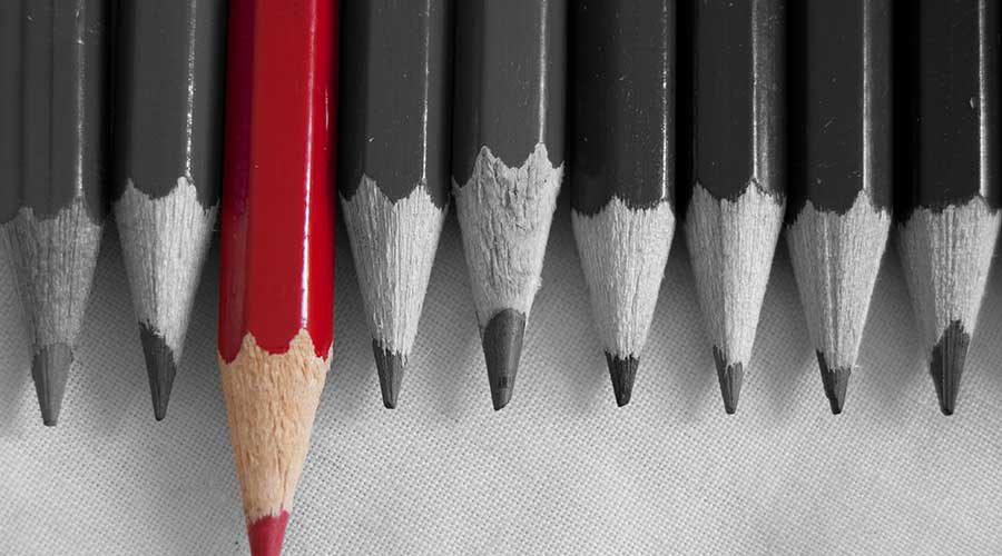 קבוצת עפרונות שחורים ואחד אדום בולט קדימה