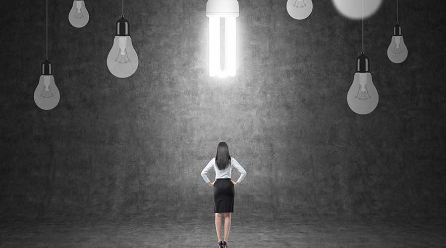 אישה עומדת עם הגב למצלמה מתחת לנורות חשמל גדולות מאוד