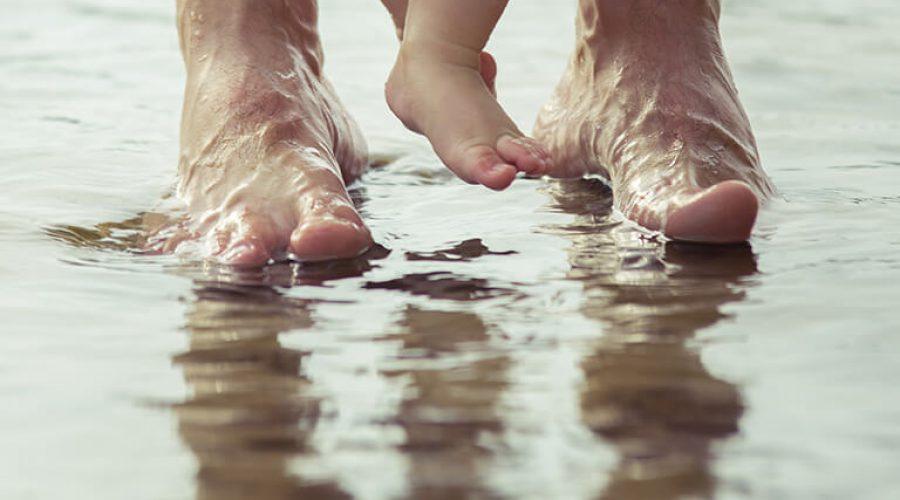 רגליים של מבוגר ותינוק על מאגר מים