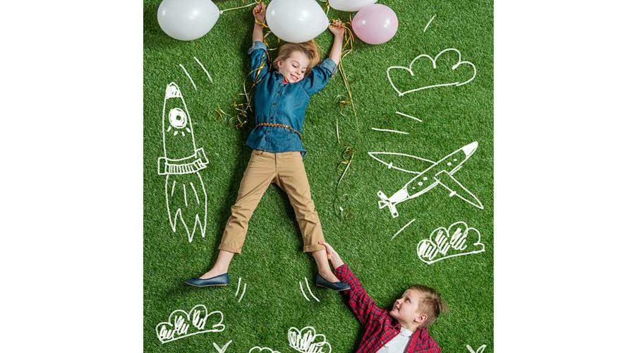 שני ילדים שוכבים על דשא עם בלונים