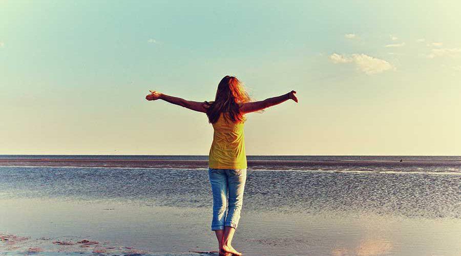 אישה פורשת ידיה מול הים
