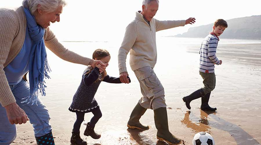 סבים ונכדים משחקים בכדור בחוף הים