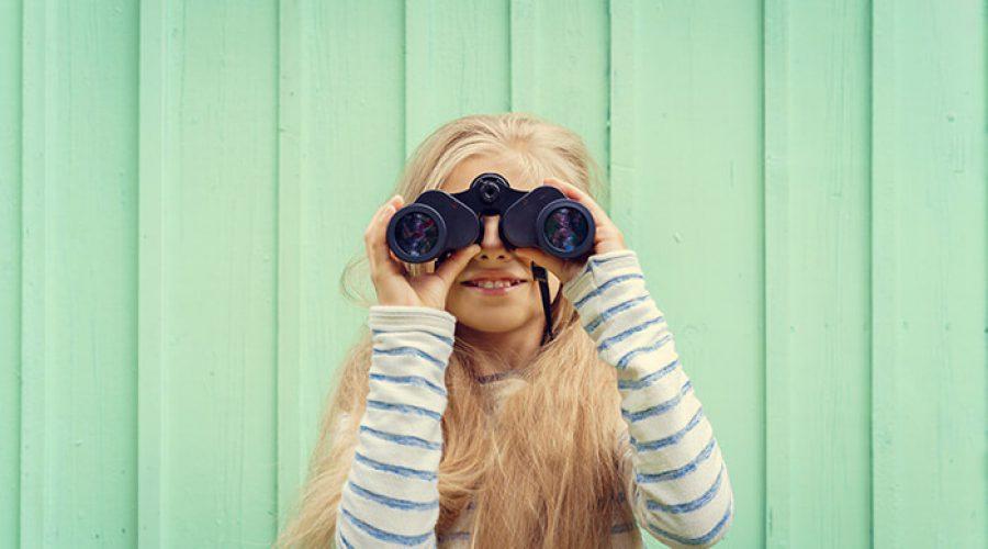 ילדה מביטה דרך משקפת