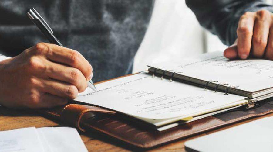 גבר בחליפה כותב ביומן