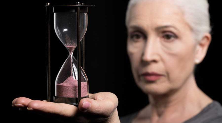 אישה מחזיקה שעון חול על כף ידה