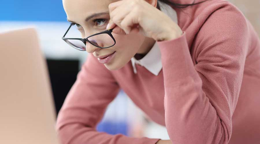 נערה במשקפיים מביטה במסך מחשב