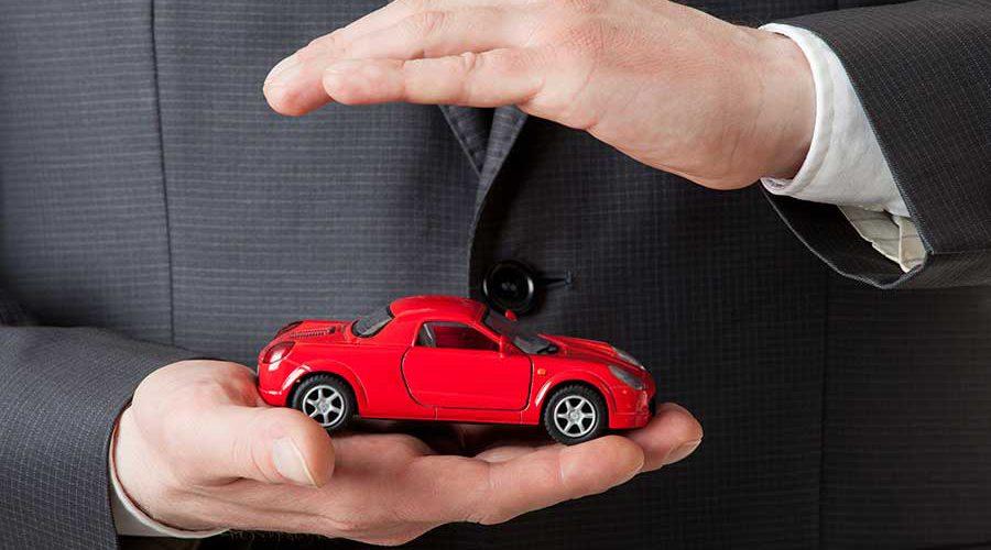 שתי ידיים מחזיקות רכב צעצוע אדום
