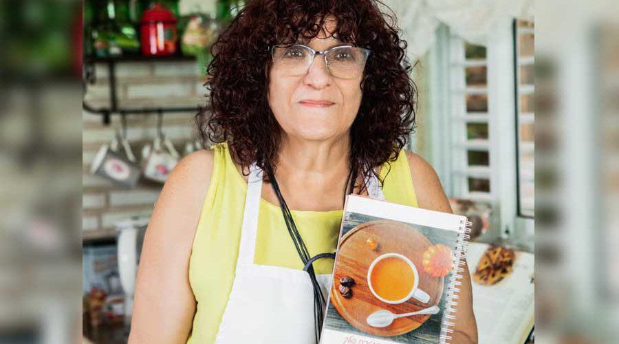 יהודית לוטואק מחזיקת את ספר המתכונים הראשון שכתבה