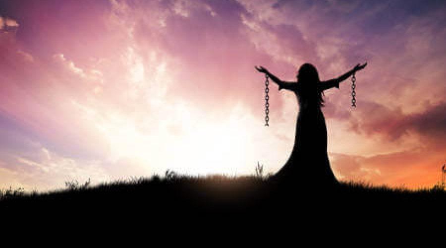אישה מרימה ידיים לרקע שקיעה