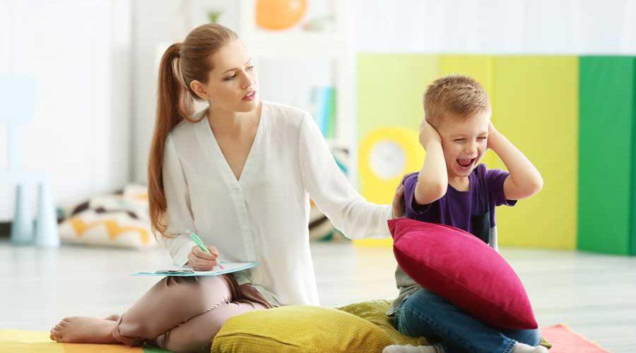 ילד מחזיק את אוזניו ואימו לידו