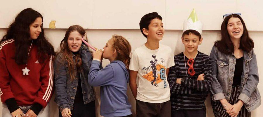 קבוצת ילדים נשענים על קיר
