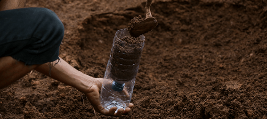 אדם ממלא אדמה בבקבוק פלסטיק