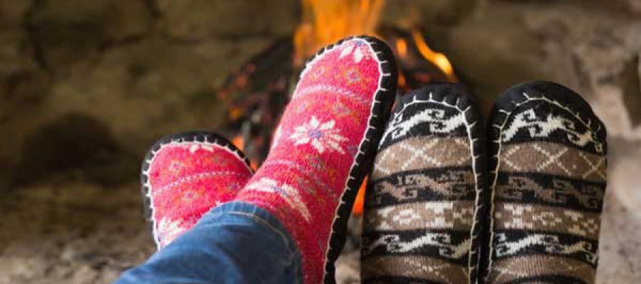 זוג רגליים בנעלי בית מול אח דלוק