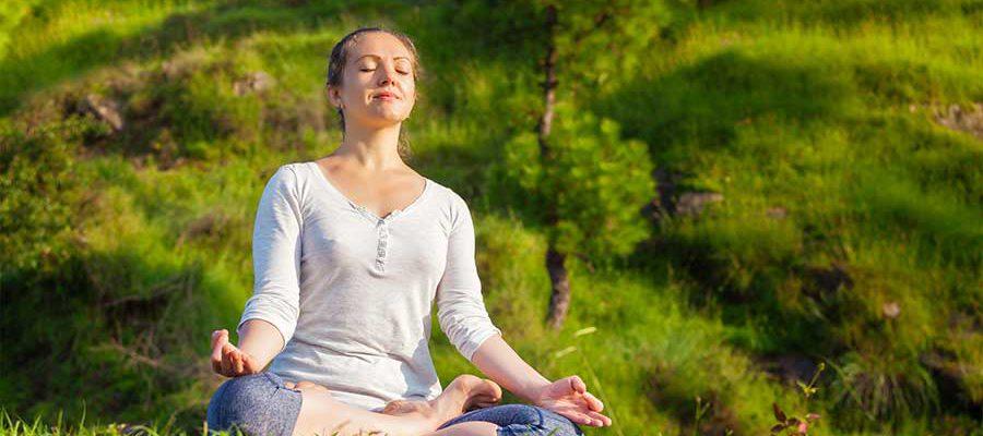 אישה בתנוחת מדיטציה בטבע