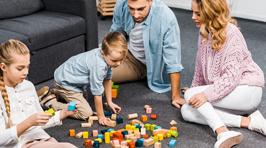 משפחה משחקת במשק קופסא על השטיח