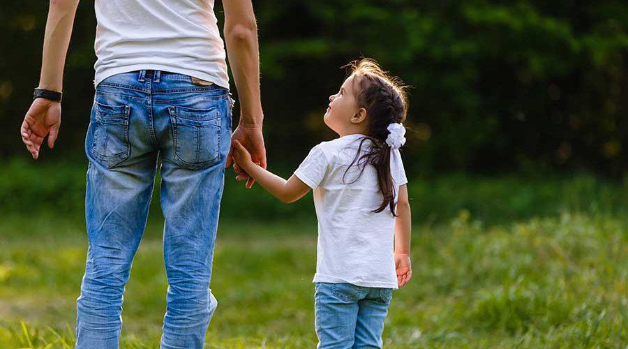 אב וילדה מחזיקים ידיים בשדות