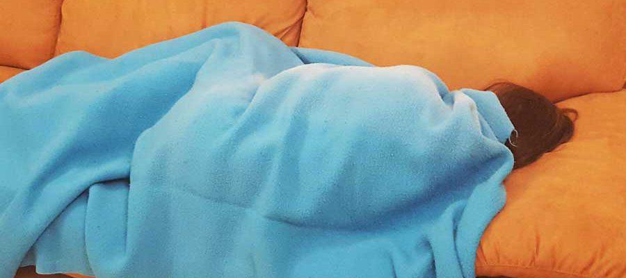 ילדה מכוסה בשמיכה שוכבת על ספה