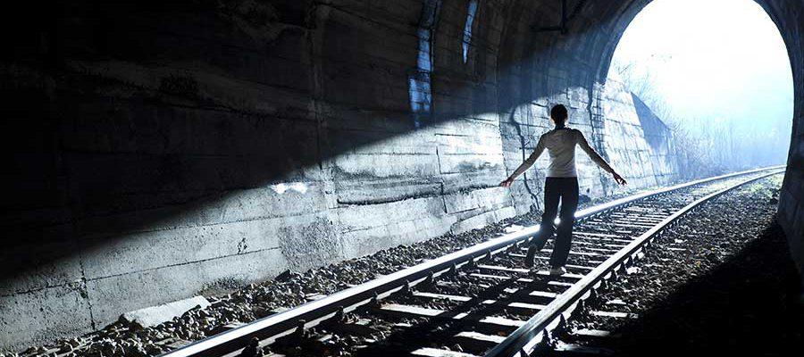 דמות פוסעת על פסי רכבת בתוך מנהרה