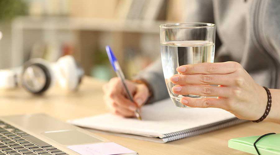 אישה כותבת ומחזיקה כוס מים