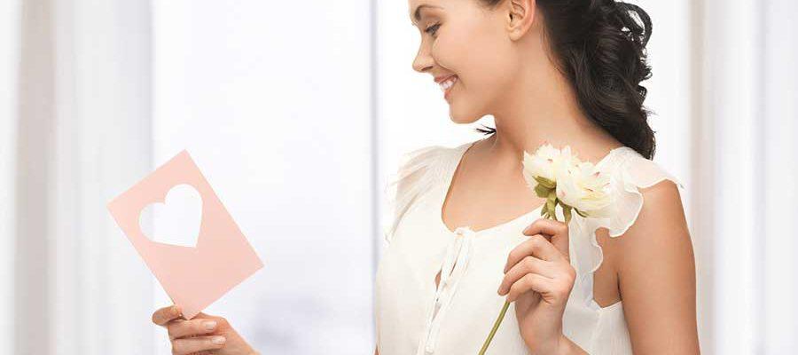 אישה מחזיקה פרח ביד אחת וכרטיס ברכה ביד שנייה