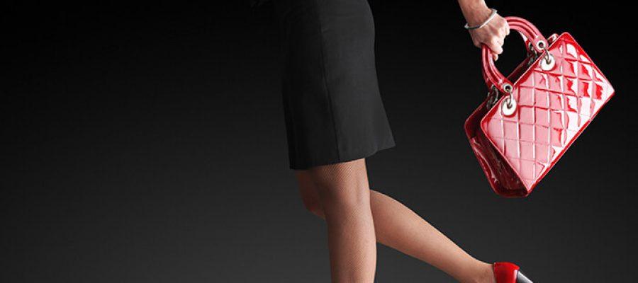 אישה בשמלה שחור עם תיק יד אדום