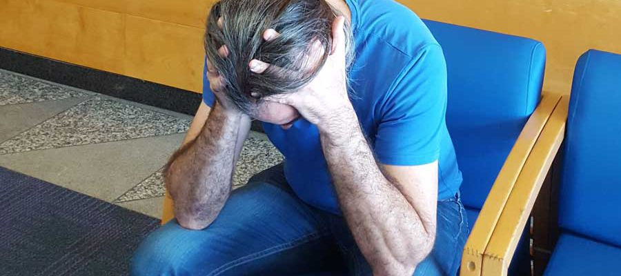 גבר יושב ומחזיק את ראשו בידיו