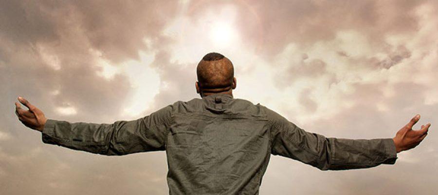 גבר פורש ידיים מעליו עננים